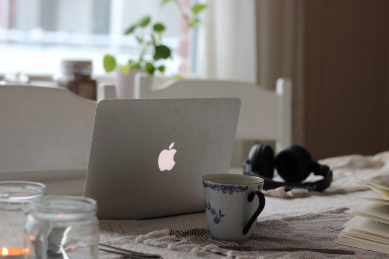 MacBook, Kaffekopp, levande ljus, hörlurar från pioneer,